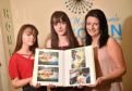 Iona, Jade and Margaret McWilliam with pictures of Jade's time in hospital