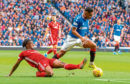 Alfredo Morelos and Greg Leigh in action during the Premiership clash at Ibrox