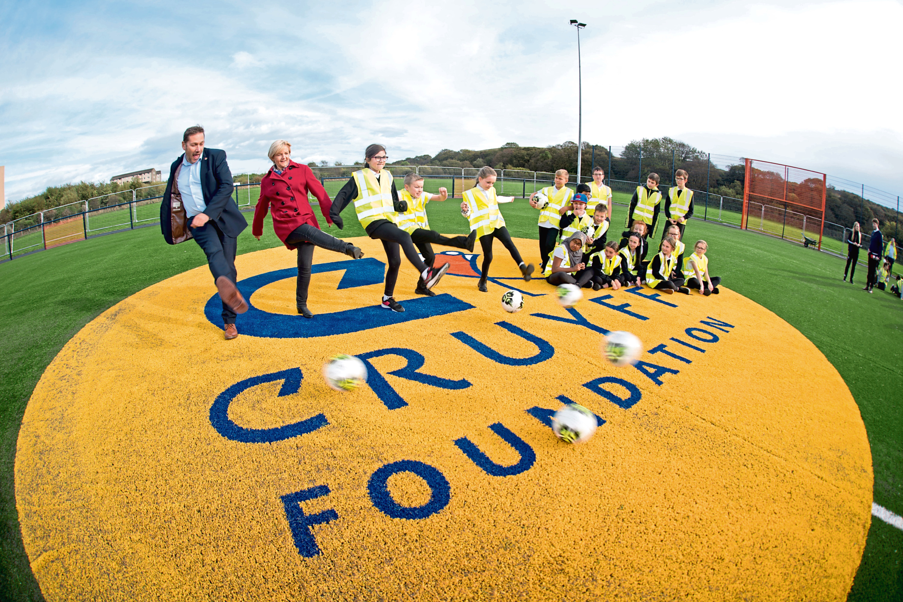 Councillor Jenny Laing and Councillor Douglas Lumsden try out the pitch with help from Tullos Primary School