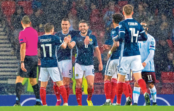 James Forrest, Mikey Devlin and goalscorer John McGinn are pictured celebrating making it 3-0 during the qualifier between Scotland and San Marino