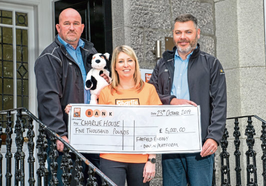 Alan Reid and Doug McFarlane presenting a cheque to Kirsty Walker of Charlie House
