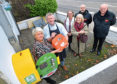 Placing the new defibrillator are, from left, Donna Coutts and Kenny Milne, Paula Fogiel and Meg Thomson, who helped find the location, and Scott Douglas and Ian Shearer from Comcab