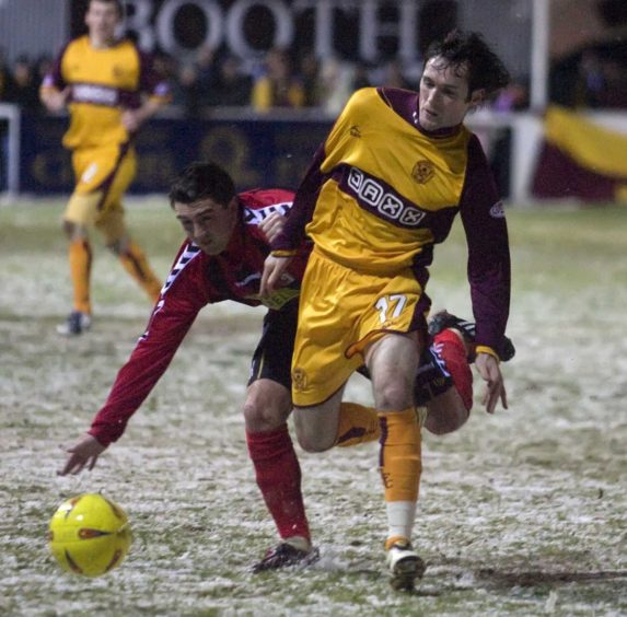Motherwell's Jim O'Brien (right) sends current Locos captain Neil McLean tumbling to the floor.