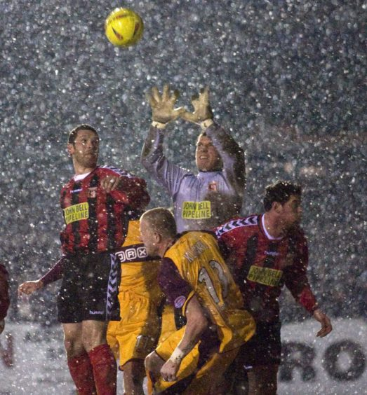 Current Inverurie Locos keeper Andy Reid (centre) tries to claim a cross under pressure from Maros Klimpl (13) and against adverse weather.