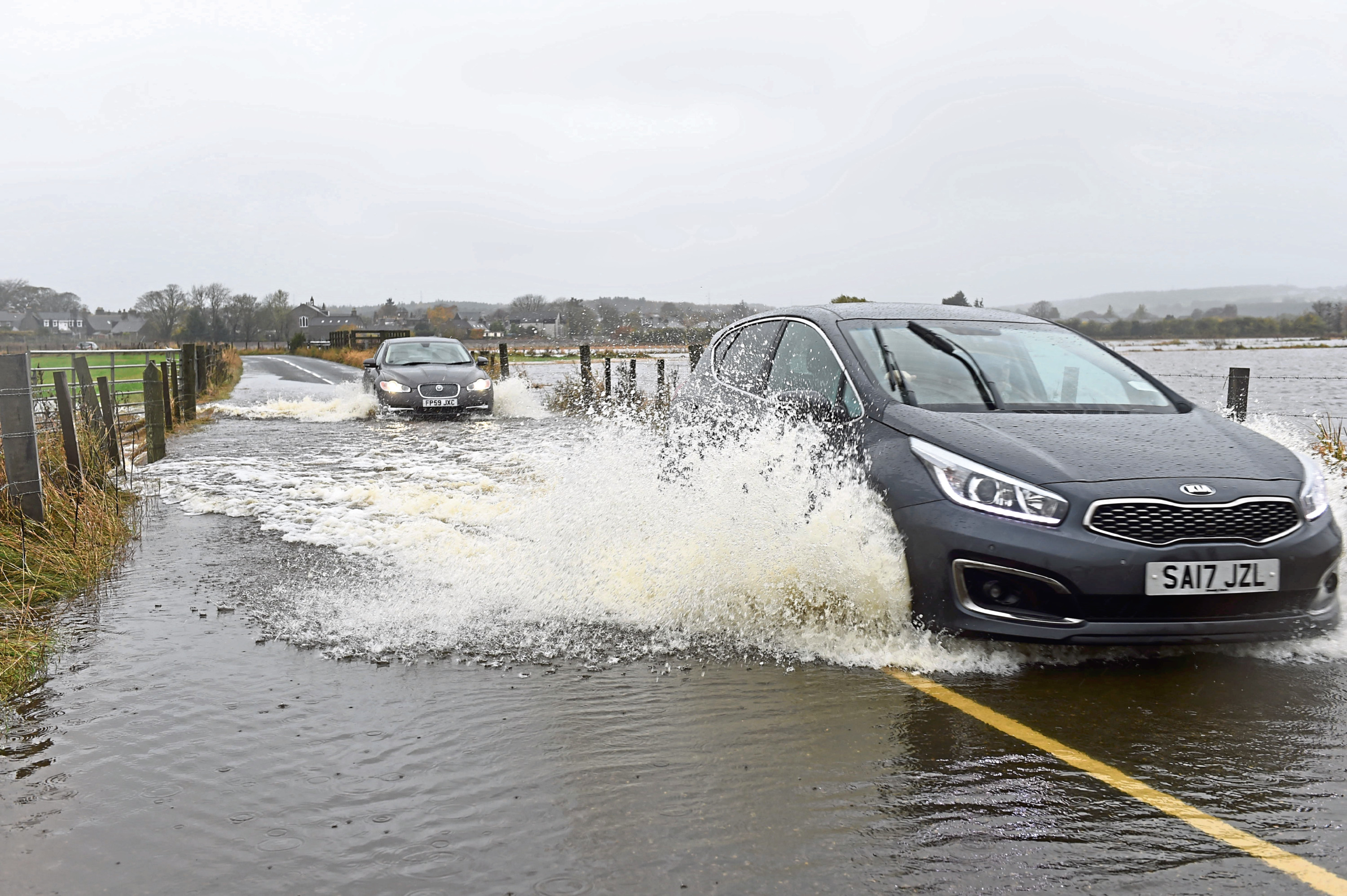 Cars attempt to make their way through the flooded road before it was closed
