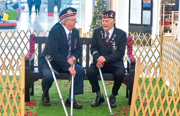 Veterans Terry McDade, left, and Jim Pirie try out the new memorial bench located at the Trinity Centre