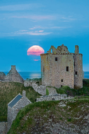 A supermoon reflected tin the water as it rises over Dunnottar Castle, taken by Veli Bariskan