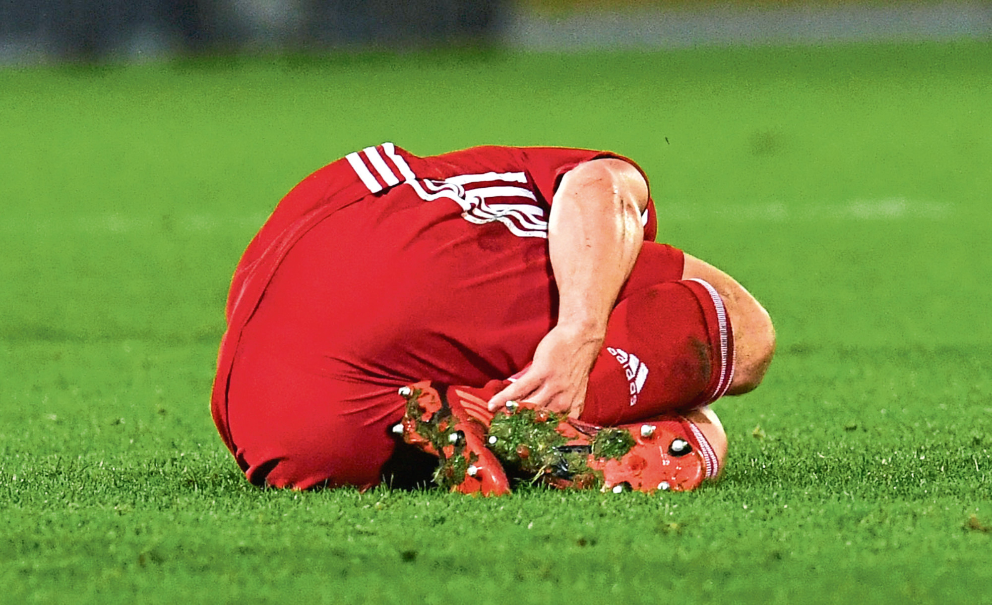 Aberdeen's Craig Bryson lies on the McDiarmid Park turf after a tackle from St Johnstone's Murray Davidson. The Saints player was dismissed as a result.