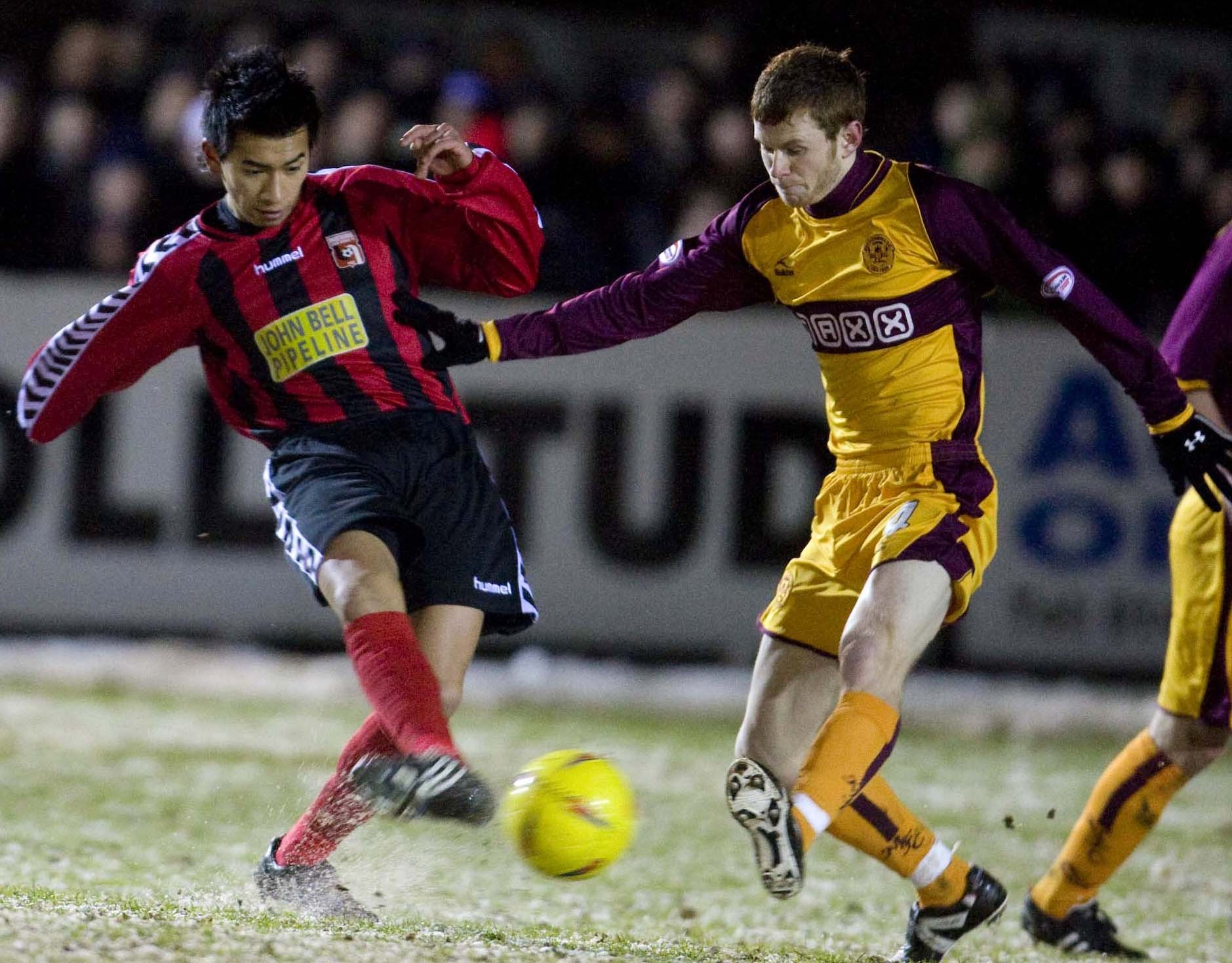 Inveruries Locos Vietnamese star Thanh-Tan Tran braves the cold as he tries to slide the ball past Mark Reynolds.