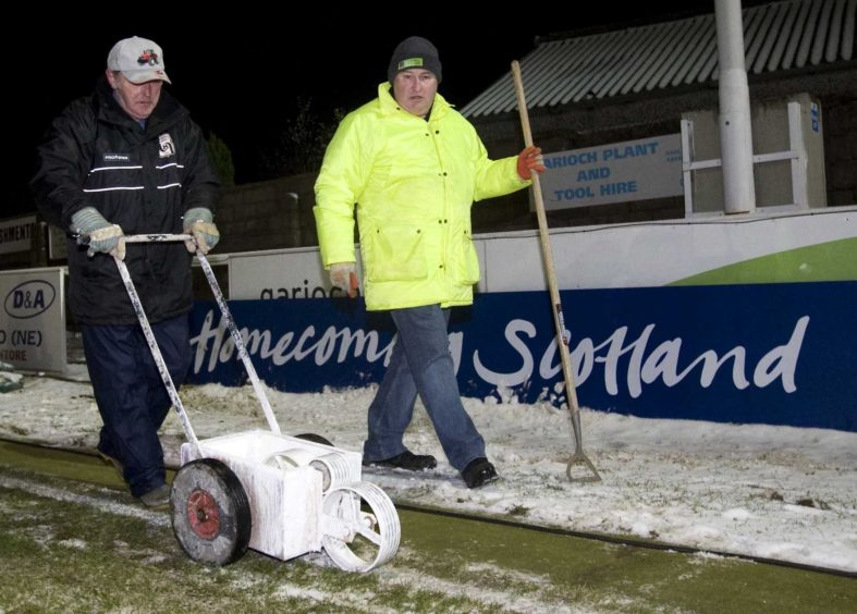 The ground staff at Harlaw Park lay the lines after heavy snowfall caused the picth to be covered ahead of the Homecoming Scottish Cup fourth round clash.