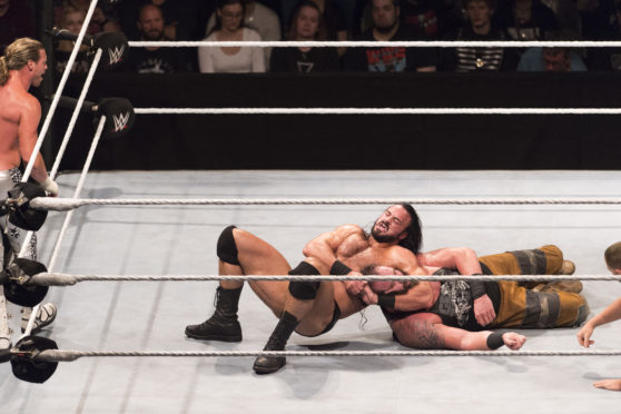 Drew McIntyre competes in the ring against Braun Strowman.