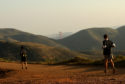 Two runners compete in The North Face Endurance Challenge Championships in the Marin Headlands, with San Francisco's Golden Gate Bridge in the distance.