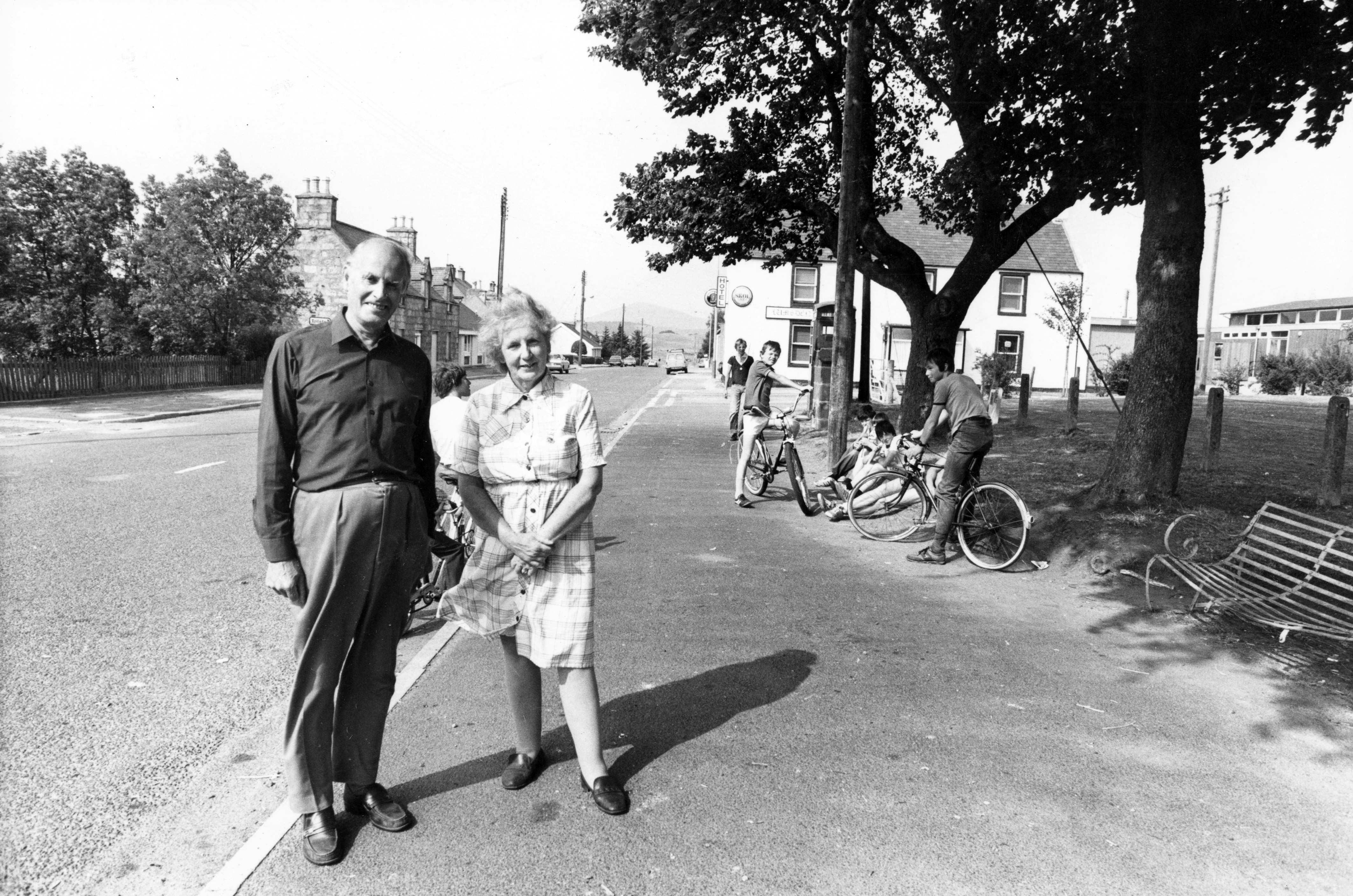 Malcolm and Susan Gray in the Main Street, with the village green to the right, and the Tap o' Noth in the distance