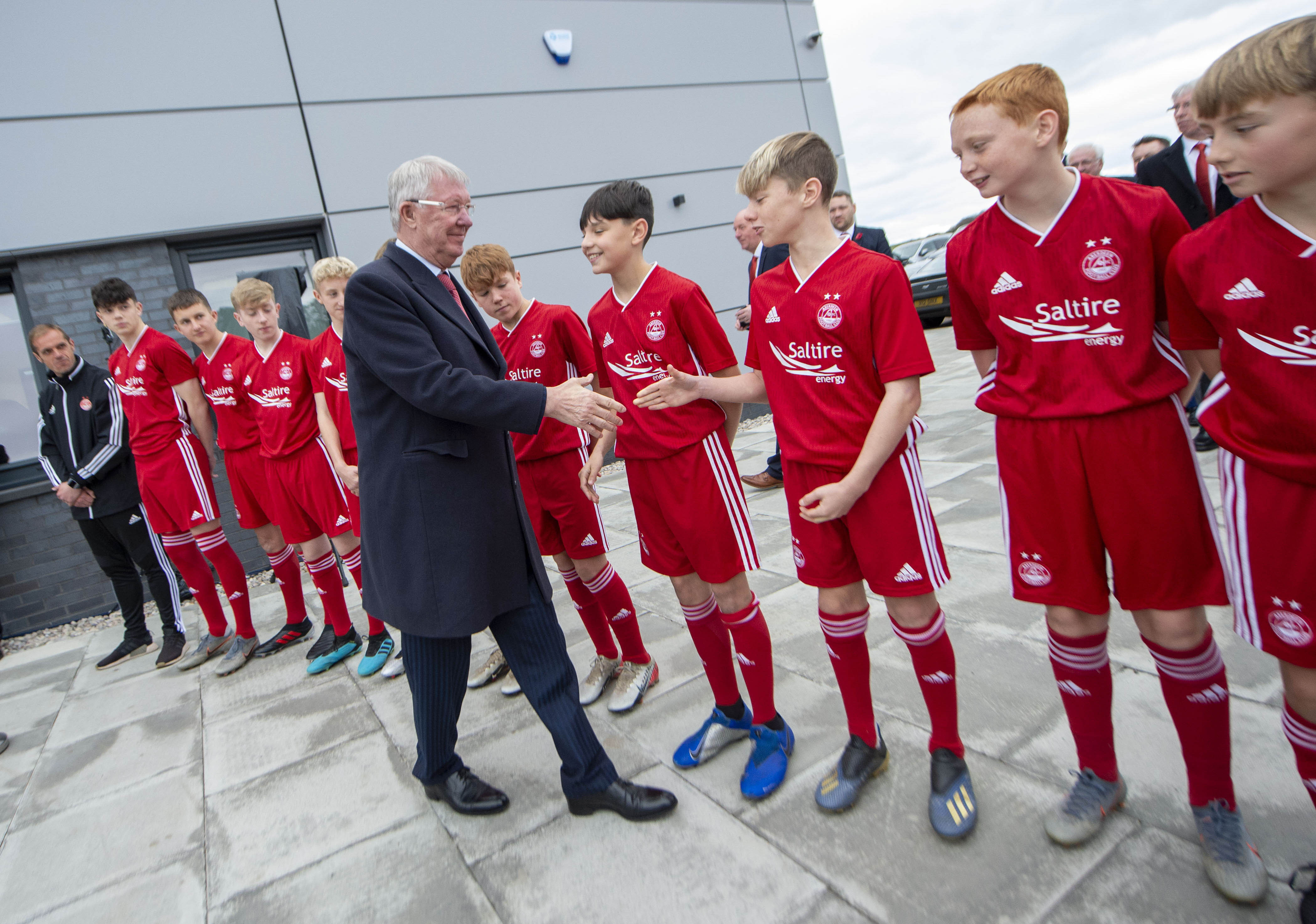 Former Aberdeen and Manchester United manager Sir Alex Ferguson shakes hands with young Aberdeen players during the official opening of Cormack Park.