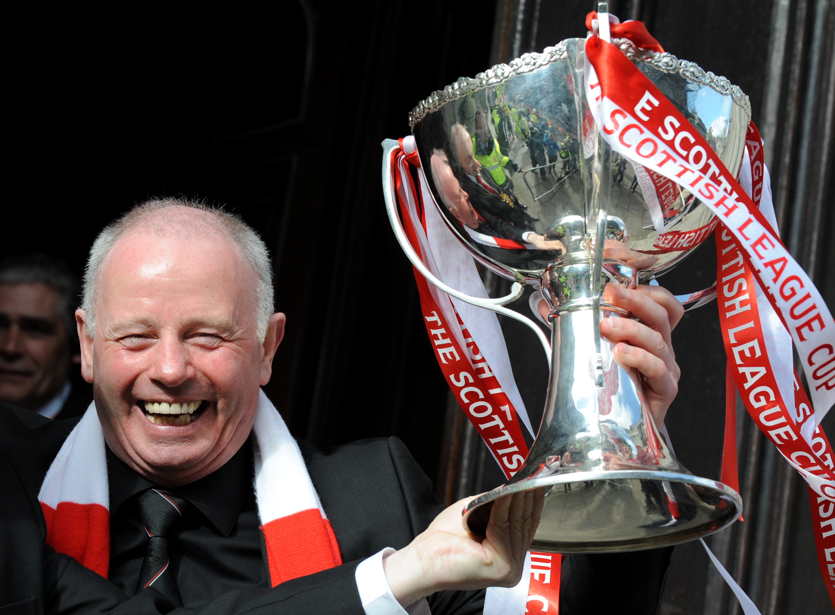 Stewart Milne holds the Scottish League Cup, won by the Dons in 2014, during a celebratory bus trip