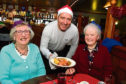 Peterhead FC manager Jim McInally serves up the turkey to Eleanor Walker, left, and Daisy Duncan at the first Balmoor Christmas lunch