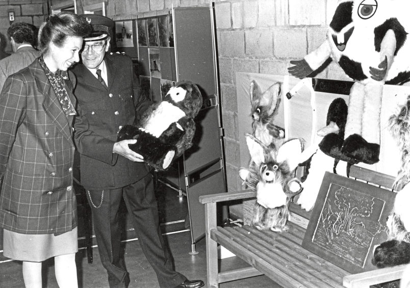 Princess Anne at Peterhead Prison with soft toys and art by prisoners
