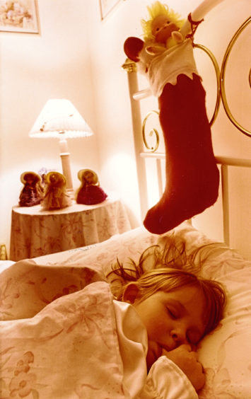 A child sleeps soundly before Christmas, while a stocking filled with toys hangs on their bed