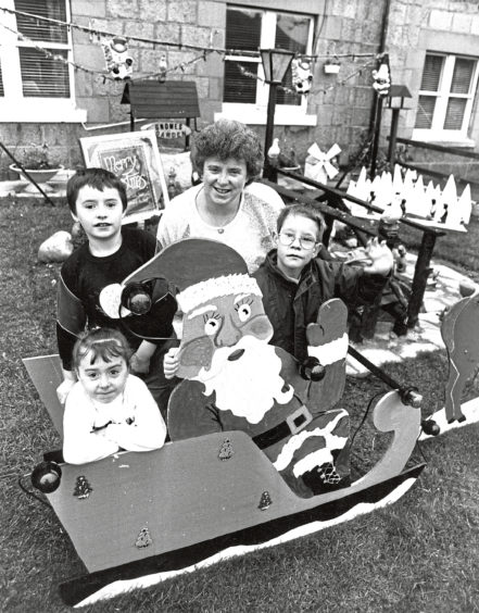 1989: Eight-year-old Craig Wiseman, right, gets ready for the big switch-on in Leonard and Gloria Mackay's front garden in School Road, Aberdeen. Gloria's children, John, 9, and Kelly, 5, enjoy a sleigh ride in the display