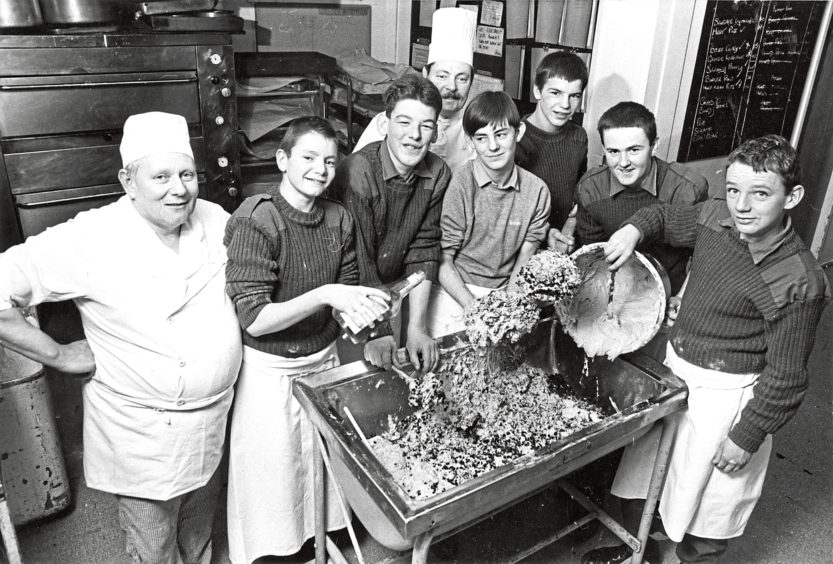 1980: Staff Quarter Master Sgt Ray McAlinden, centre, is helped to bake a 200lb Christmas cake for the Evening Express senior citizens film show
