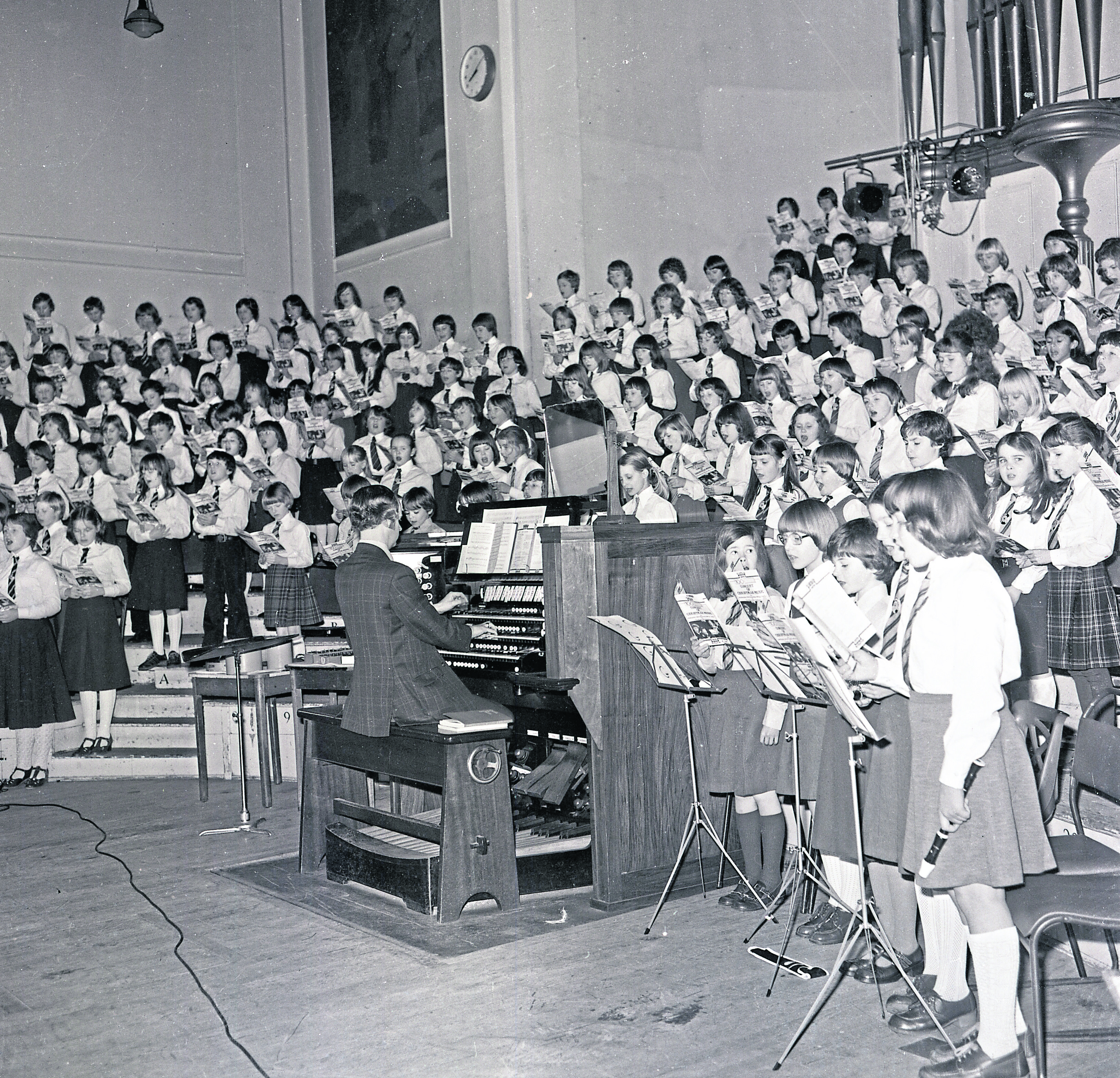 1979: An organist leading massed choirs at the 1979 carol concert show