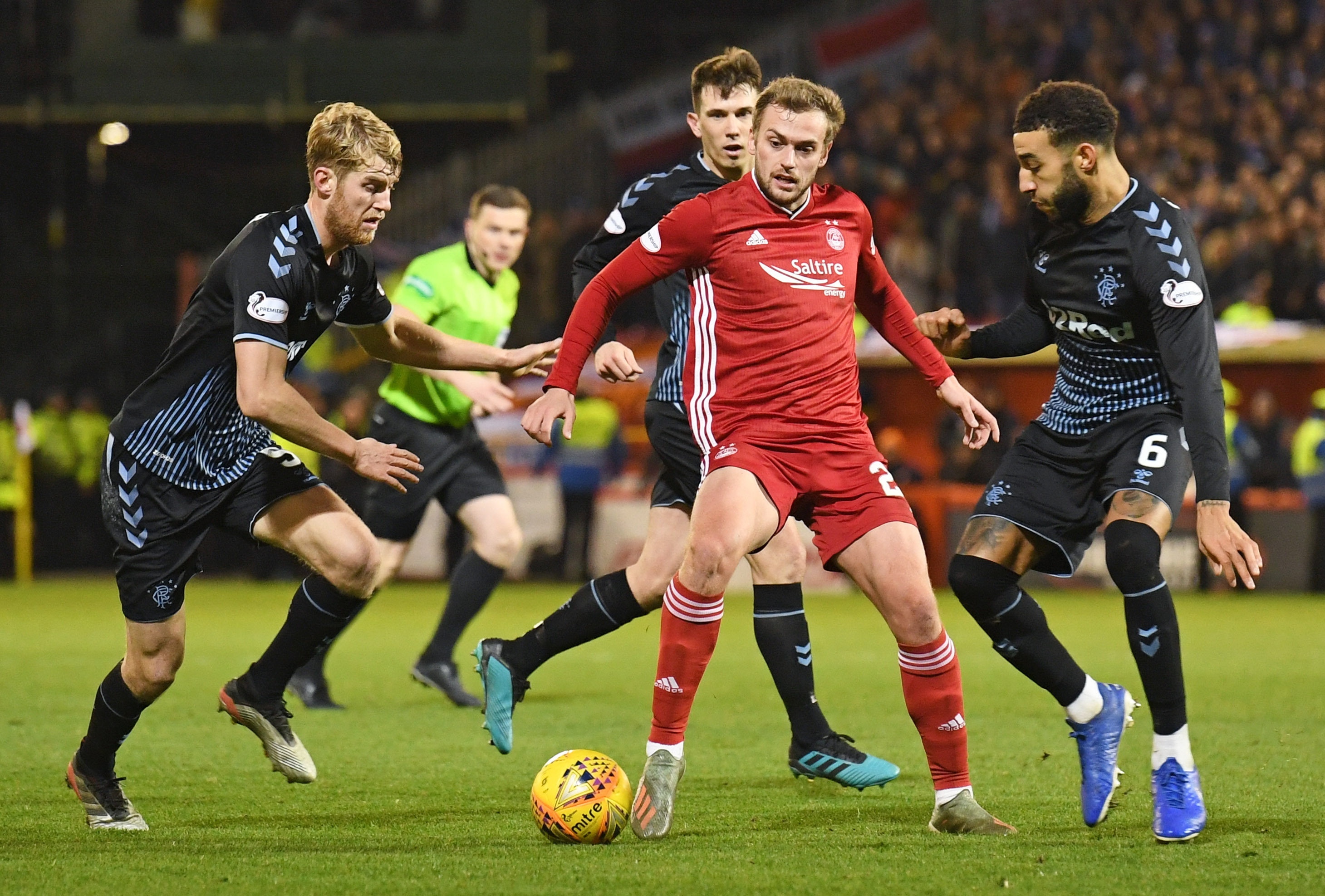 Aberdeen's James Wilson, centre, holds off Rangers' Filip Helander and Connor Goldson, right.