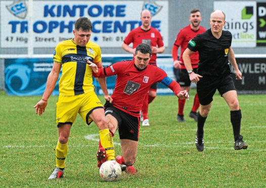 Neil McLean fires into a tackle for Inverurie.  Picture by Kenny Elrick