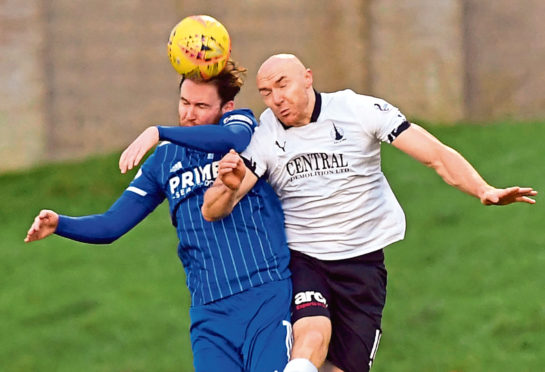 Mick Dunlop goes up for a header with Conor Sammon.