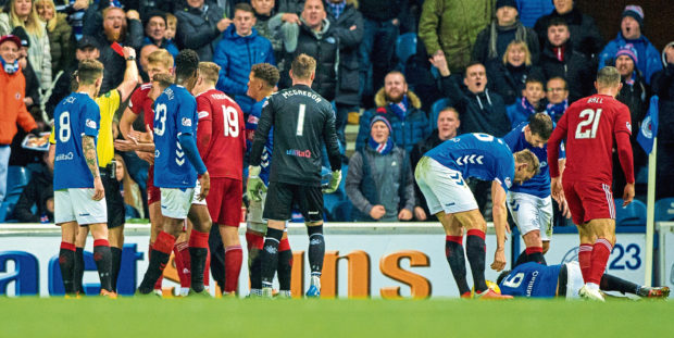 Aberdeen's Sam Cosgrove receives a red card from referee Steven McLean last season.