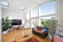 The fabulous sitting room is bright and airy with floor-to -ceiling windows overlooking the rear garden