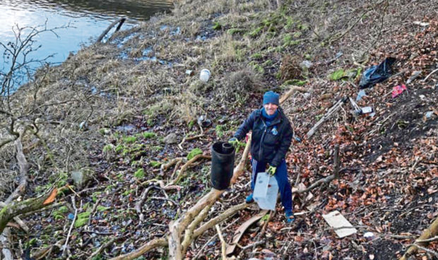 Volunteers get to work cleaning up along the banks of the River Don, bagging litter and clearing away rubbish including an old shopping trolley