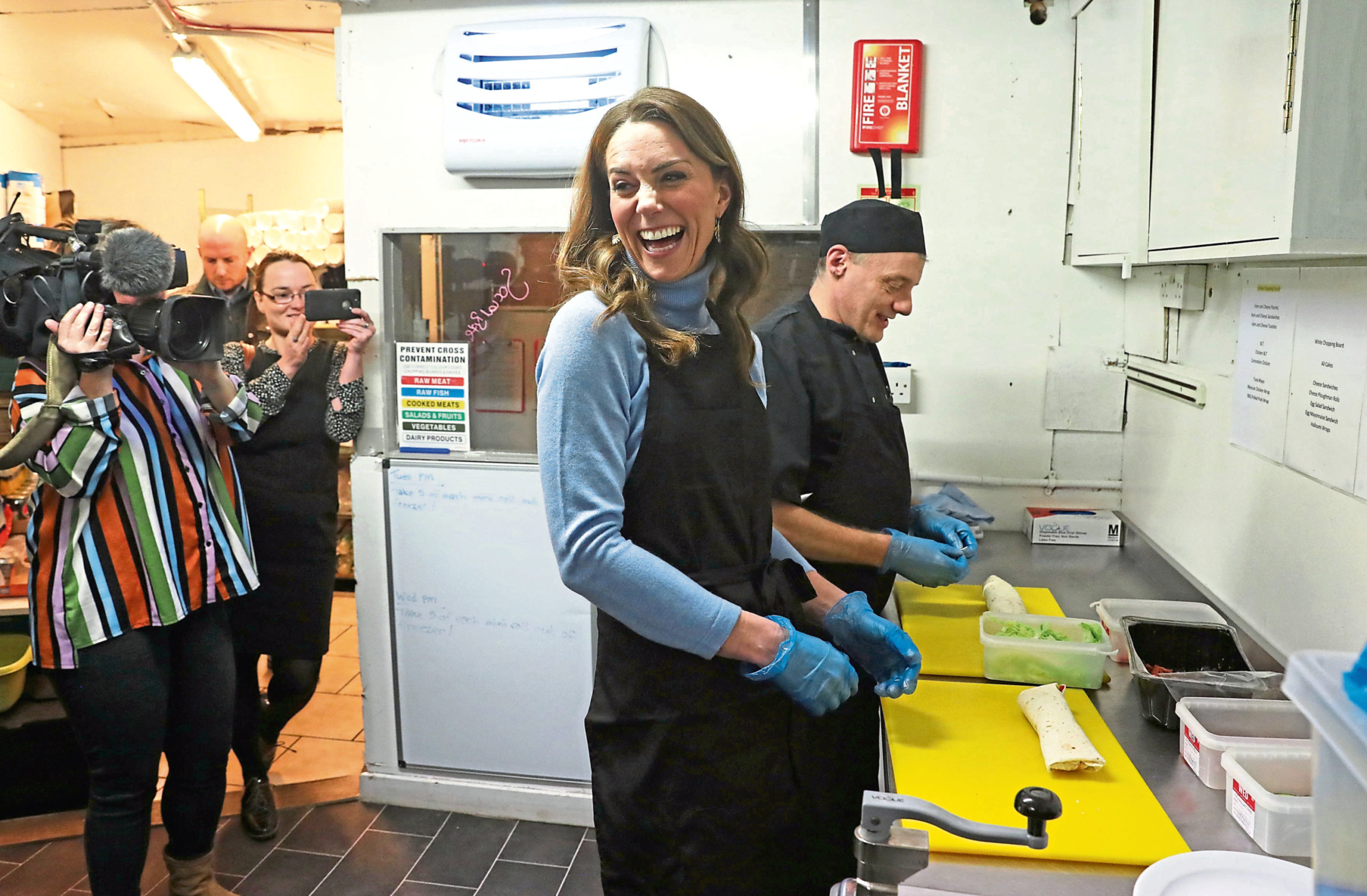 The Duchess of Cambridge, known as the Countess of Strathearn while in Scotland, helps to prepare food during a visit to the Social Bite cafe in Aberdeen