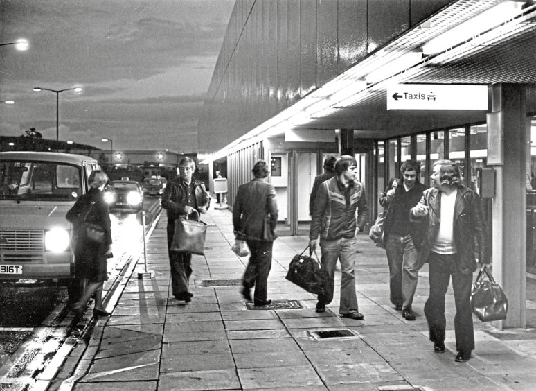 A scene that sums up the oil industry's link with the airport – workers arrive at 6.30am for the flight for Sullom Voe