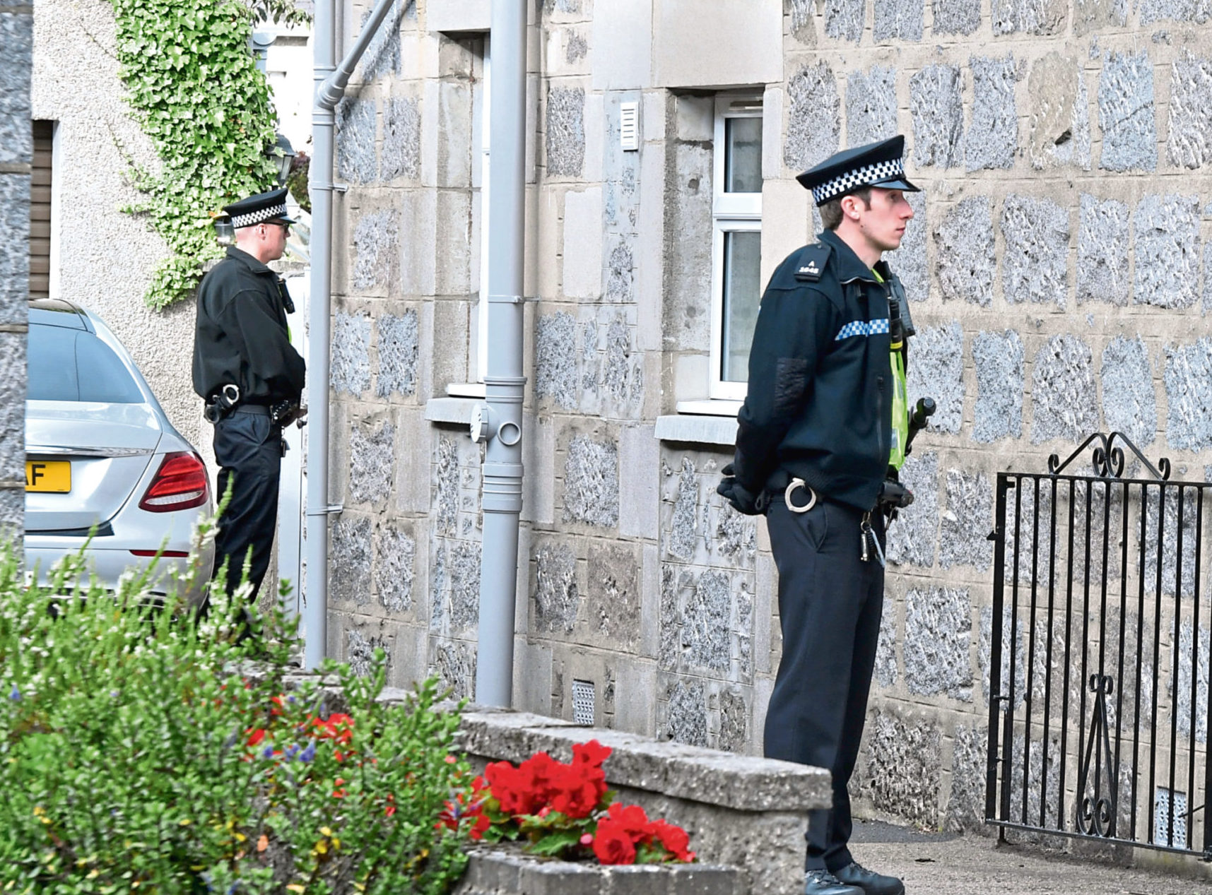 Police stand guard outside the couple's West End home