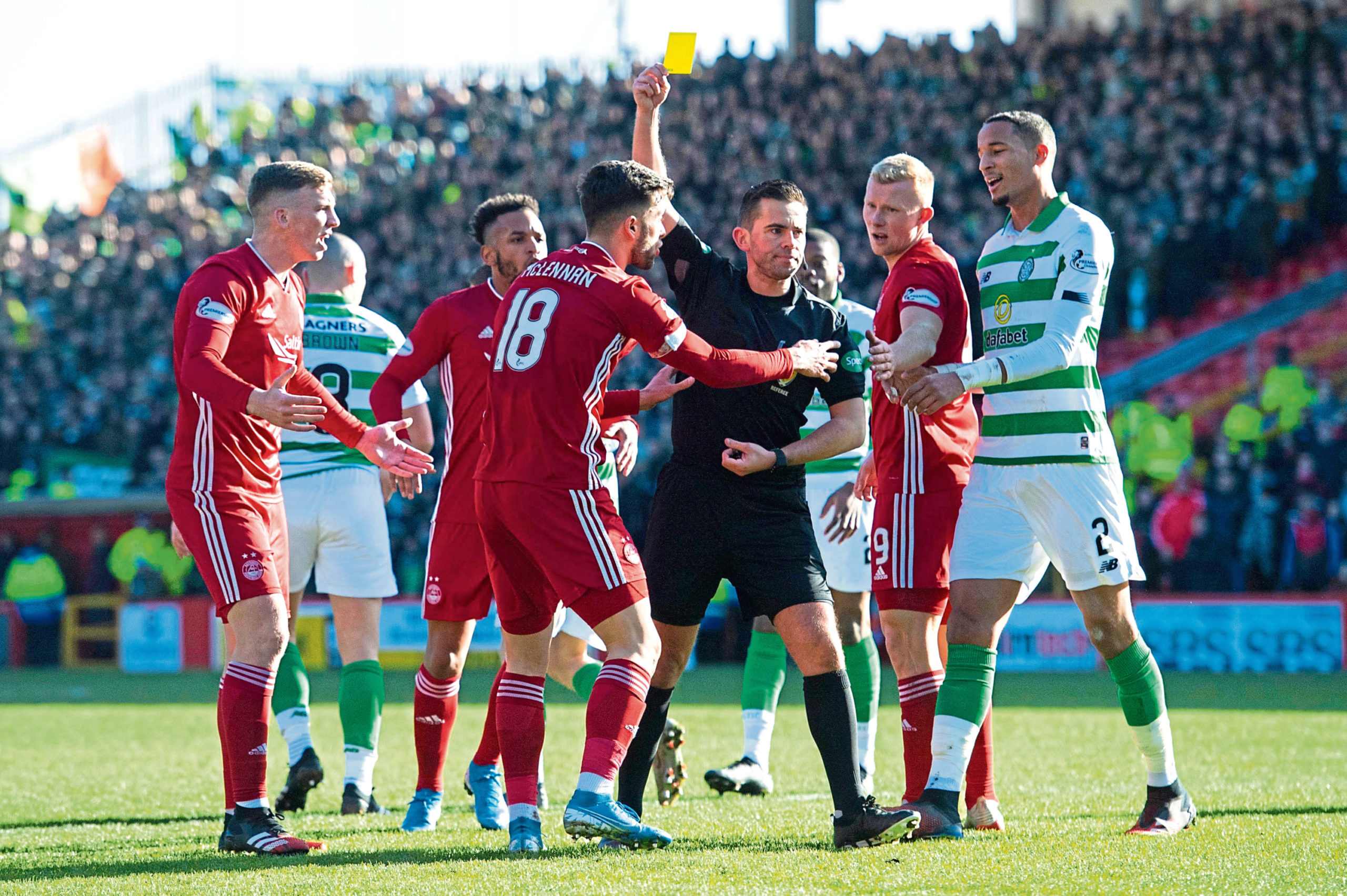 Referee Andrew Dallas show's Aberdeen's Connor McLennan a yellow card for a dive during the Ladbrokes Premiership match between Aberdeen and Celtic.