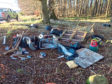 Children's toys, wooden pallets, tyres, electrical equipment and black bags were dumped in the wooded area outside Chapel of Garioch