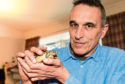 Tim with the couple's new pet, Meshell the tortoise, who his partner Kairen said loves eating red fruit
