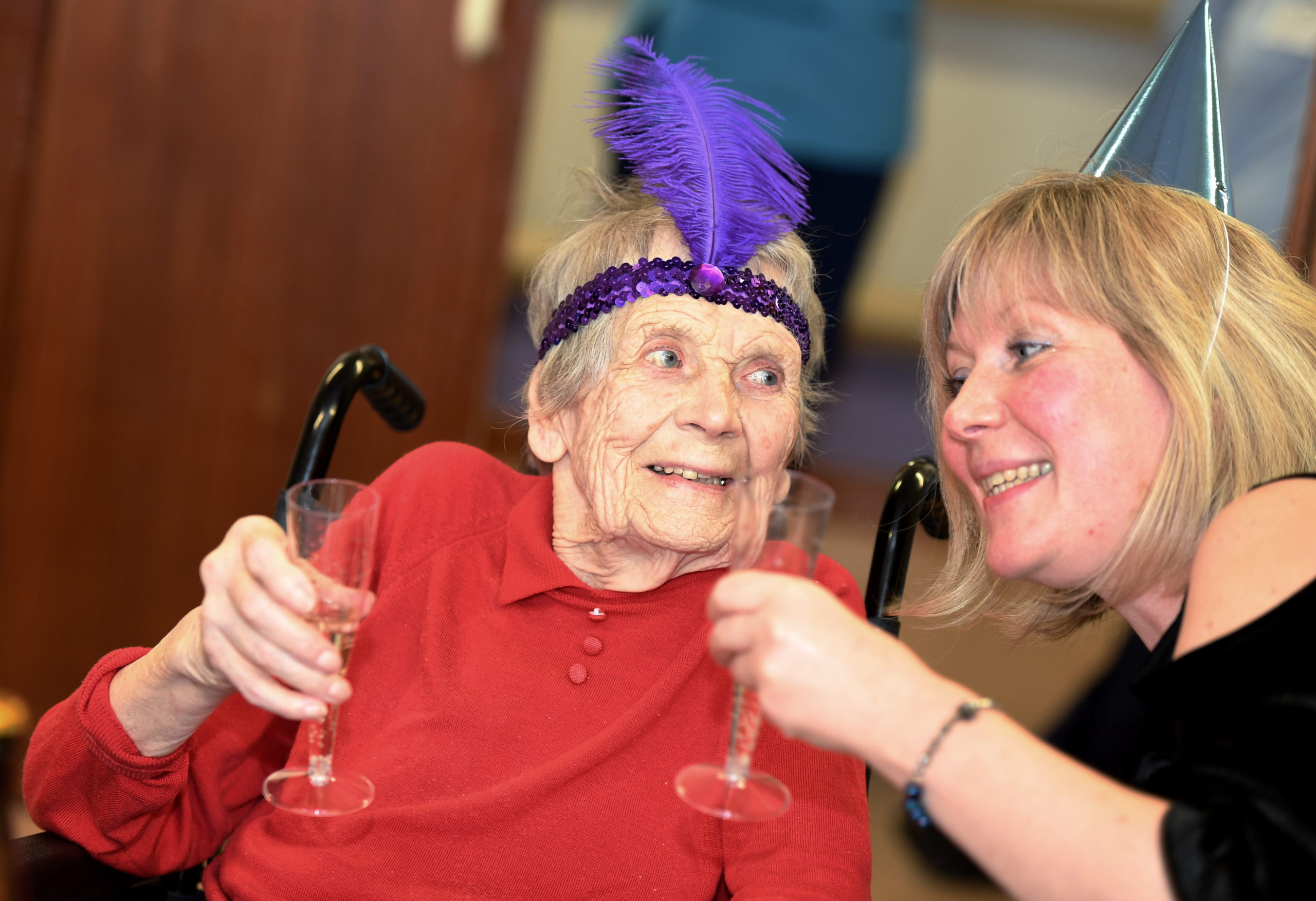 100-year-old Grace 'Bunty' MacKintosh enjoys a glass of fizz at the party with her grand-daughter Suzy. Picture by Kami Thomson