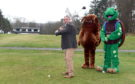 David Downie tees off at Hazlehead under the watchful eyes of the ARCHIE Foundation and Sport Aberdeen mascots. Picture by Jim Irvine