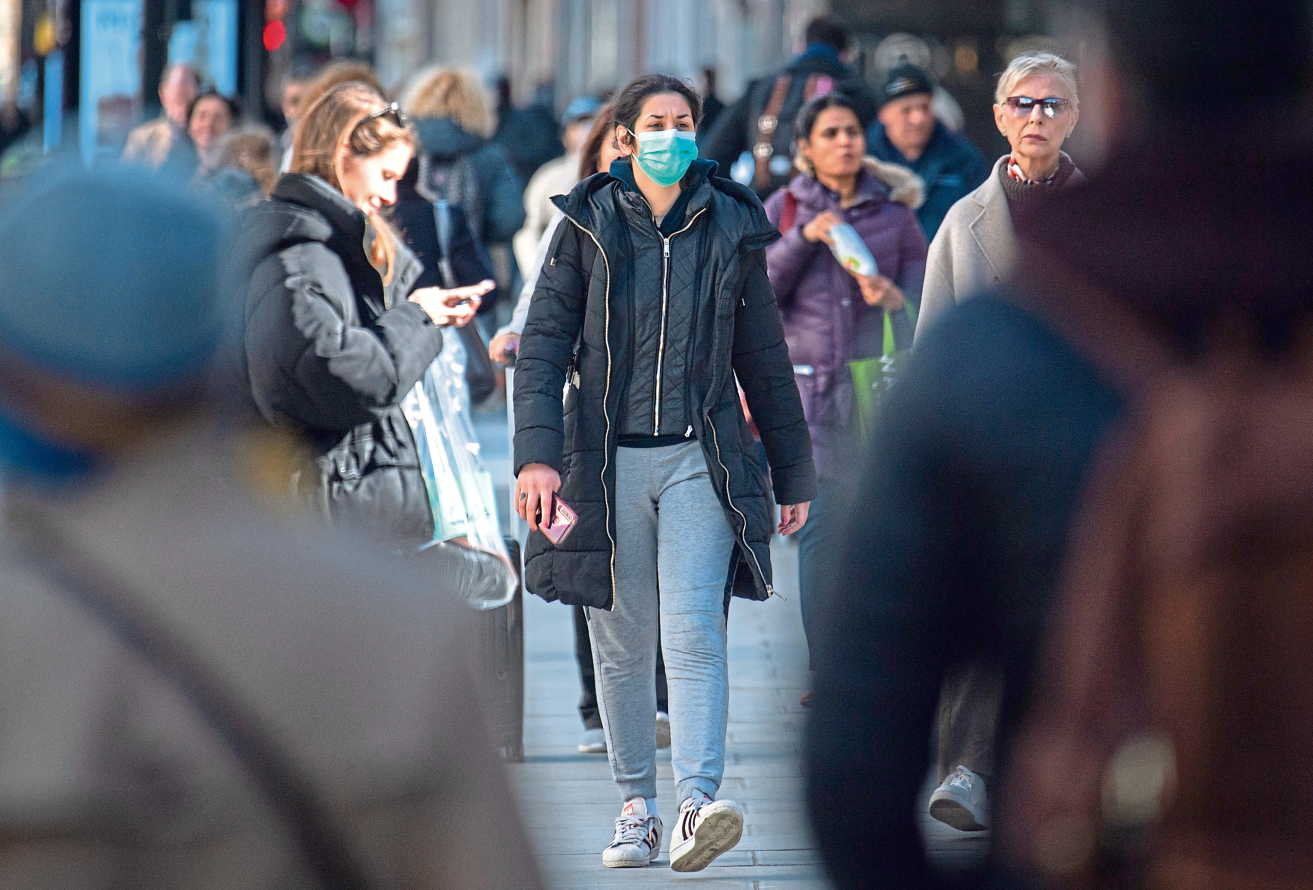 A woman in a protective face mask on Oxford Street, central London