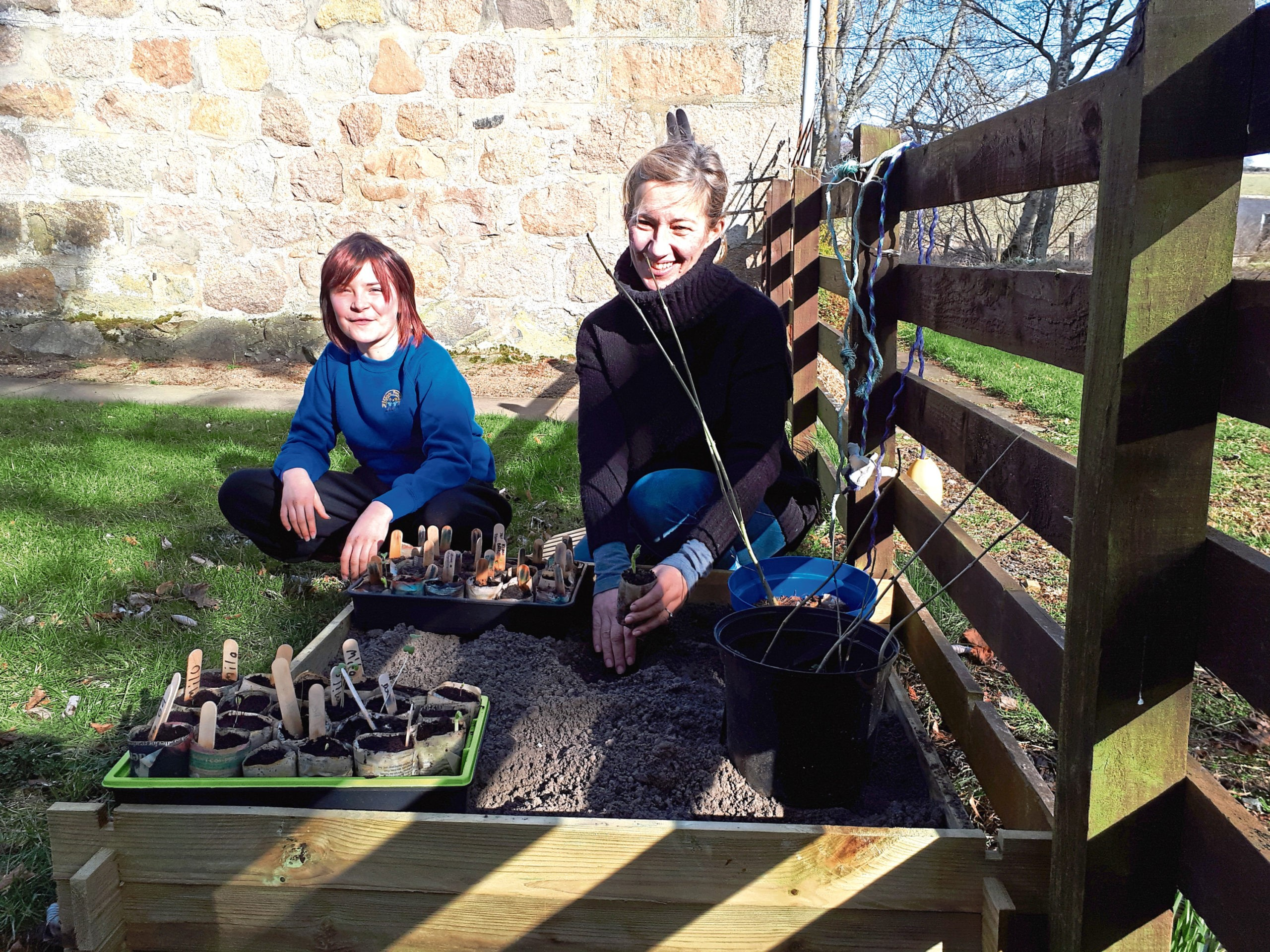 Aboyne Primary Teacher, Marianne Brooks and her daughter Rebecca planting out the seeds from our school. Luca Steven's shoot is taking the lead at 2 inches tall