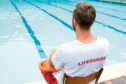 Rear view of lifeguard sitting on chair with rescue buoy at poolside; Shutterstock ID 631717046; Purchase Order: -