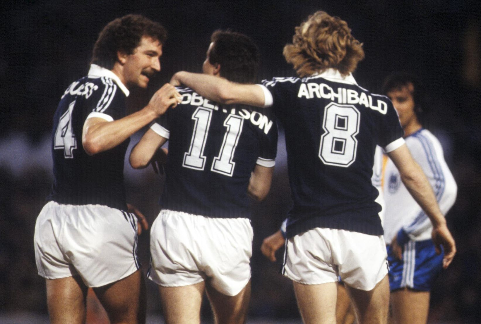Scotland winger John Robertson (centre) joins team-mates Graeme Souness (left) and Steve Archibald in celebration after his first goal.