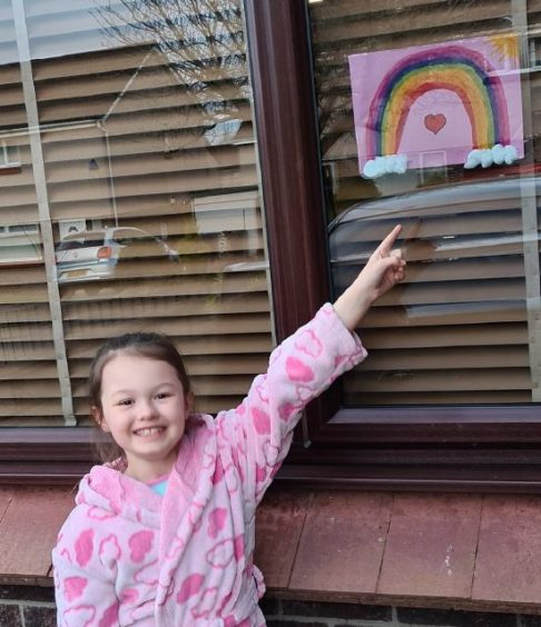 Brooke, 7, pointing to her colourful drawing