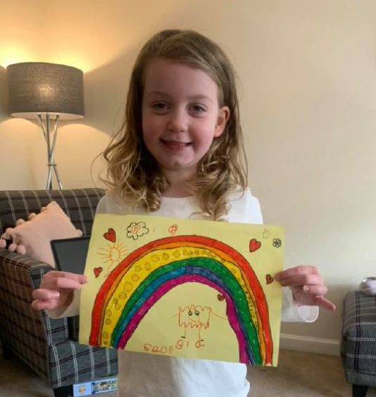Georgia, 4, holding up her rainbow drawing