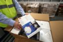 Jim Miller, Procurement Director from NHS National Services Scotland, holds a box of face masks