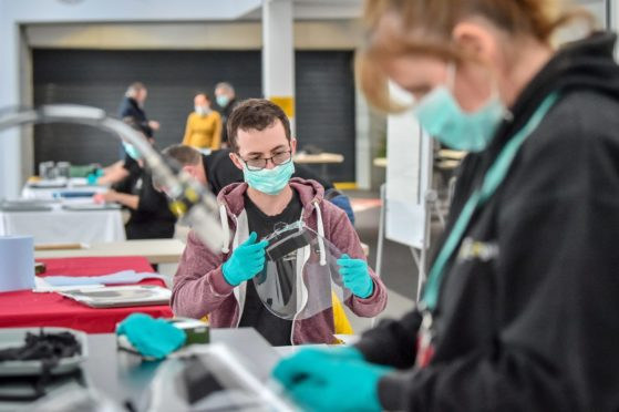 Royal Mint employees assemble full face visors in the cafe inside the Royal Mint Experience