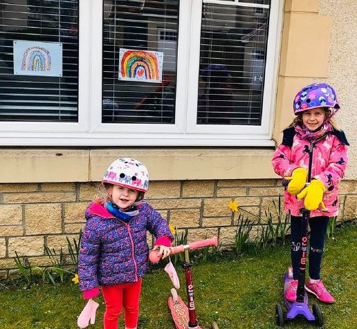 Mhairi, 5 and three-year-old Zoe playing in front of their rainbows