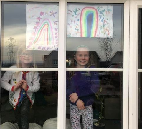 Nina, 4 and Eva 6 in their window with their rainbows