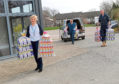 Sheena Lonchay, left, accepts Ester eggs donated at Sheddocksley Baptist Church's Fine Peace Cafe